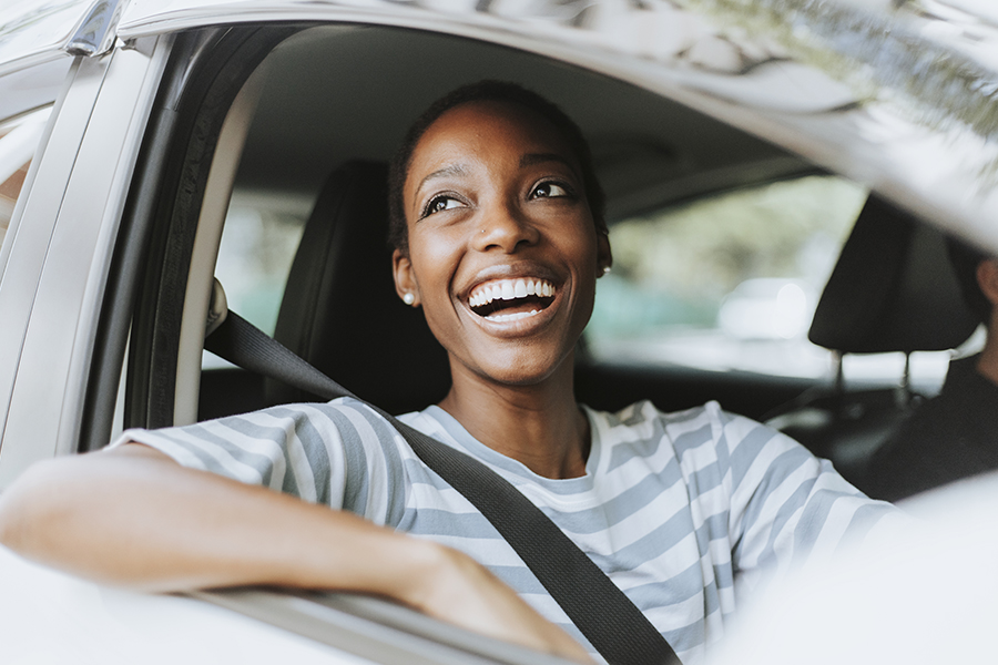 Auto Insurance - Closeup of Happy Woman Driving in a Car