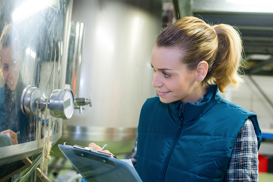 Brewery - Female Brewer Checking Brewing Process and Writing Results on a Clipboard